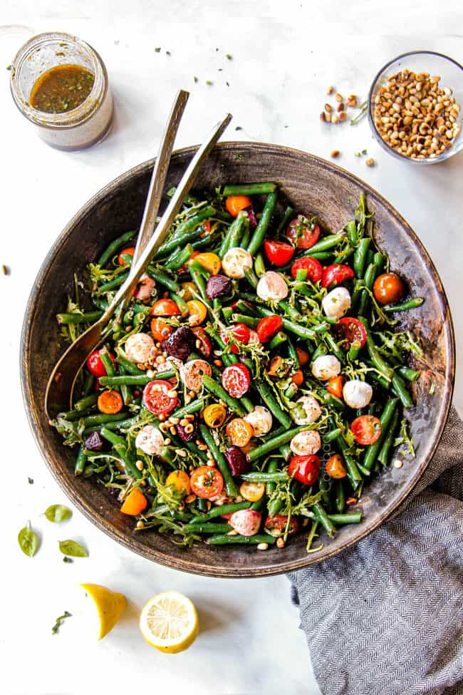top view of green bean salad recipe in a wood bowl with green beans, tomatoes, mozarella
