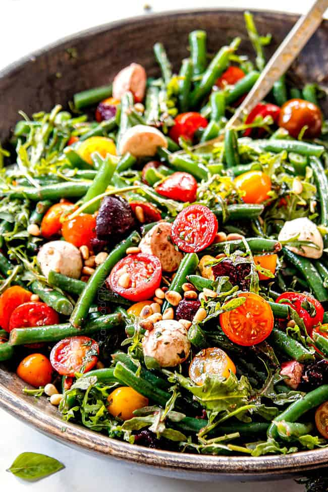 showing how to make cold green bean salad by adding green beans, tomatoes, beets to salad bowl