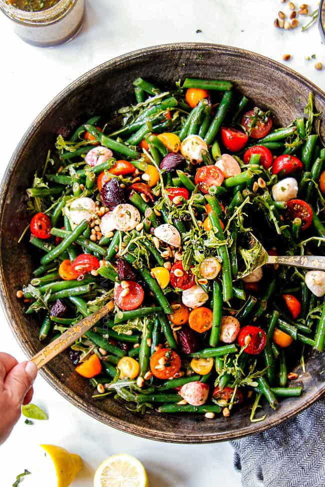 showing how to serve cold green bean salad by tossing salad with tongs