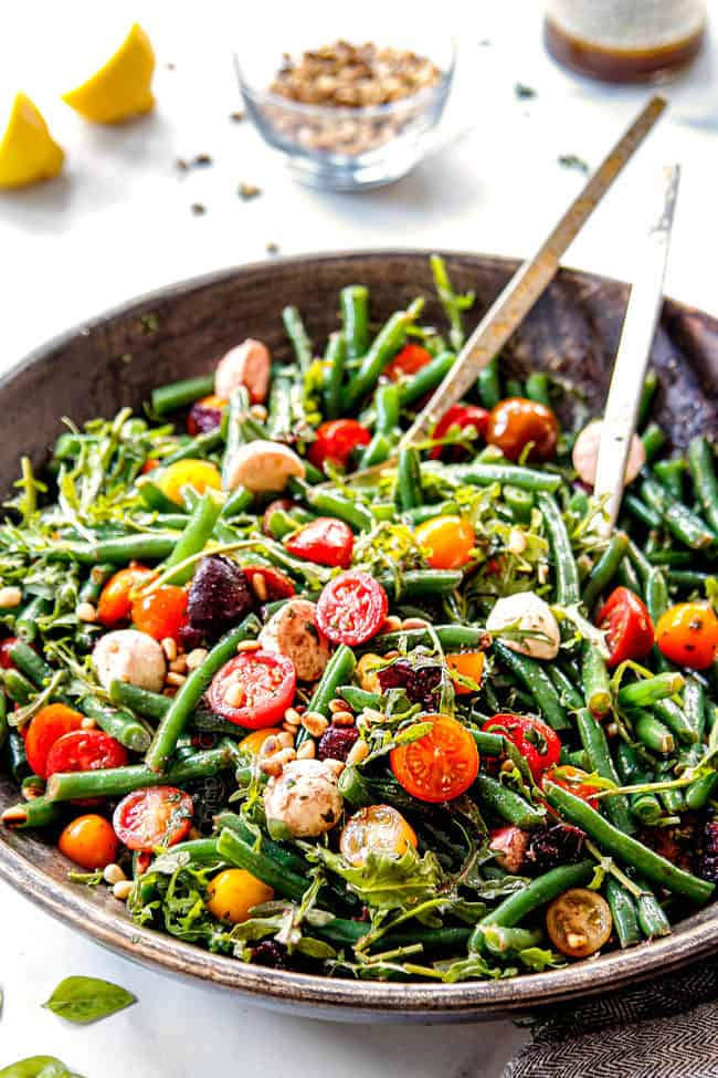 showing how to make green bean salad by tossing green beans with dressing