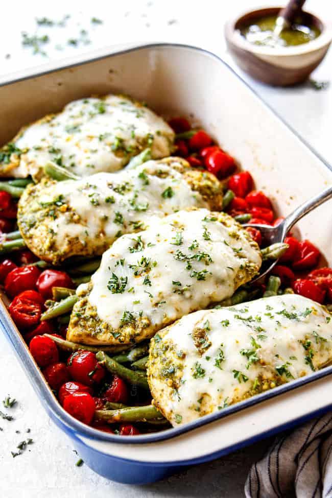 serving pesto chicken bake with mozzarella cheese