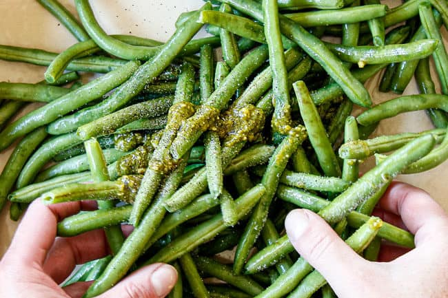 showing how to make pesto chicken by mixing green beans with pesto, olive oil, salt and pepper
