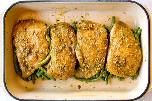 showing how to make pesto chicken bake by adding chicken on top of green beans