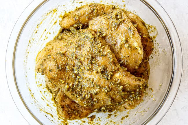 showing how to make pesto chicken by mixing chicken with pesto and seasonings