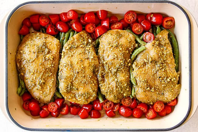 showing how to make pesto chicken recipe by lining tomatoes on sides of tomatoes