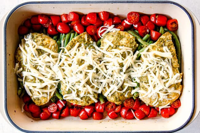 showing how to make pesto chicken bake by adding cheese on top of chicken