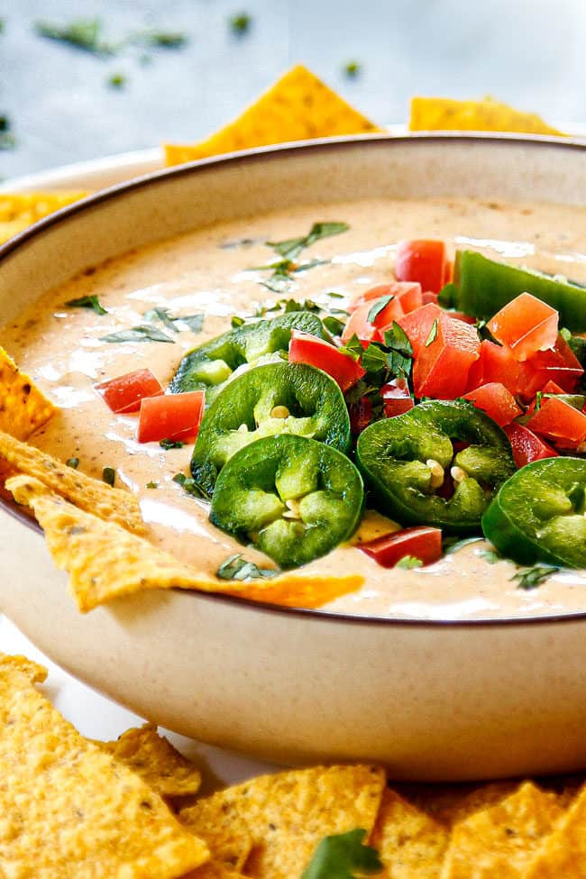 showing how to garnish White Queso Dip (Queso Blanco) by topping with jalapenos, tomatoes and cilantro