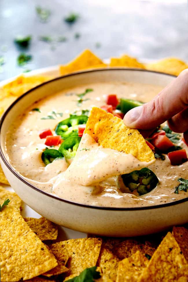 showing how to serve queso blanco recipe by dipping chip into a bowl of dip