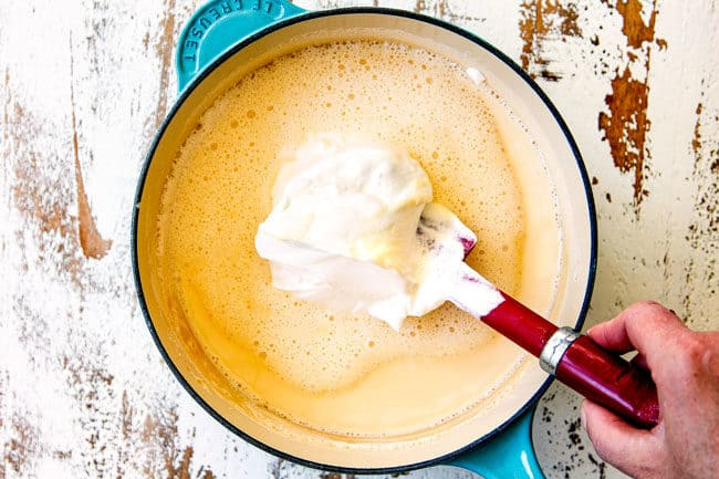 showing how to make queso blanco (white queso dip) by whisking sour cream into evaporated milk