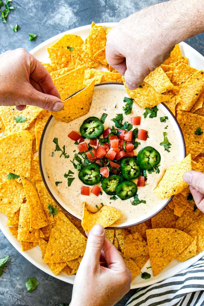 showing how to serve white queso dip by four hands dipping into a bowl of dip