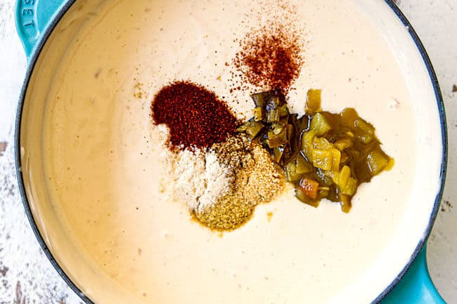 showing how to make queso blanco (white queso dip) by whisking in diced green chiles, jalapenos, chili powder, cumin, salt and pepper