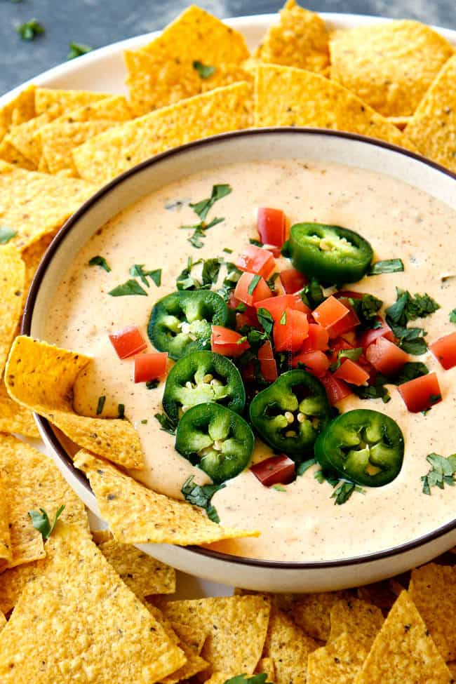 up close of queso blanco dip recipe topped with tomatoes and jalapenos surrounded by chips
