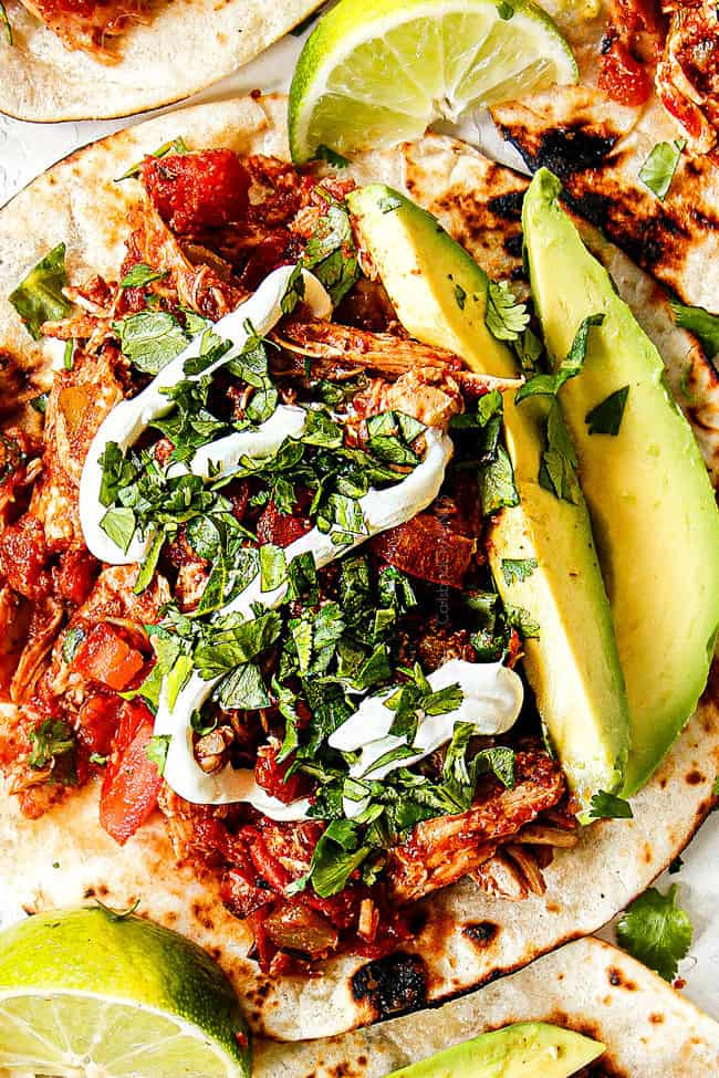 showing how to make shredded chicken tacos by adding chicken to charred tortilla