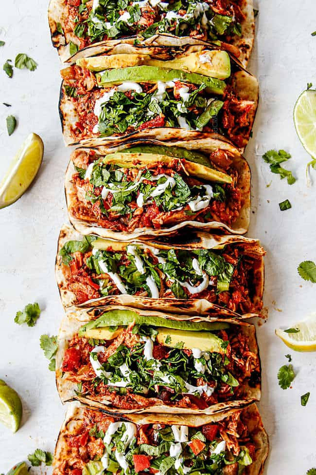 showing how to make shredded chicken tacos by making a topping bar