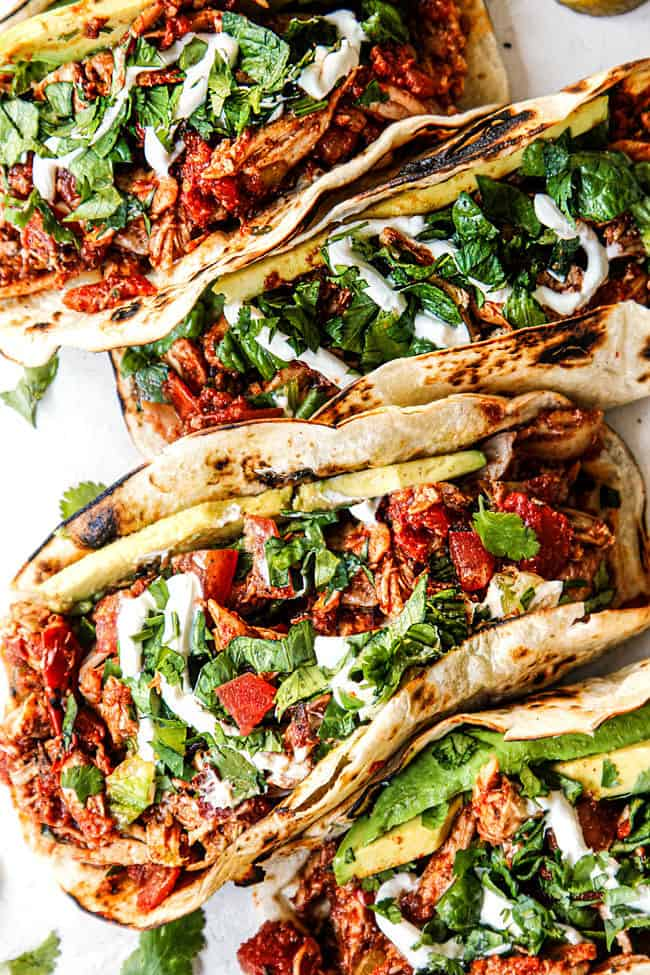 shredded chicken tacos recipe on a plate with cilantro, sour cream and avoados