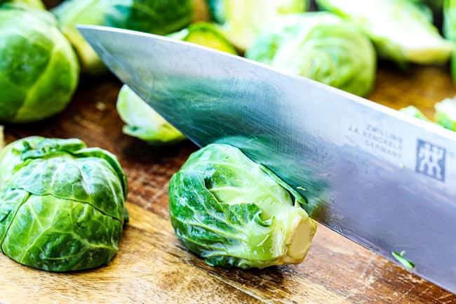 showing how to trim Brussels Sprouts on a cutting board by slicing sprout in half