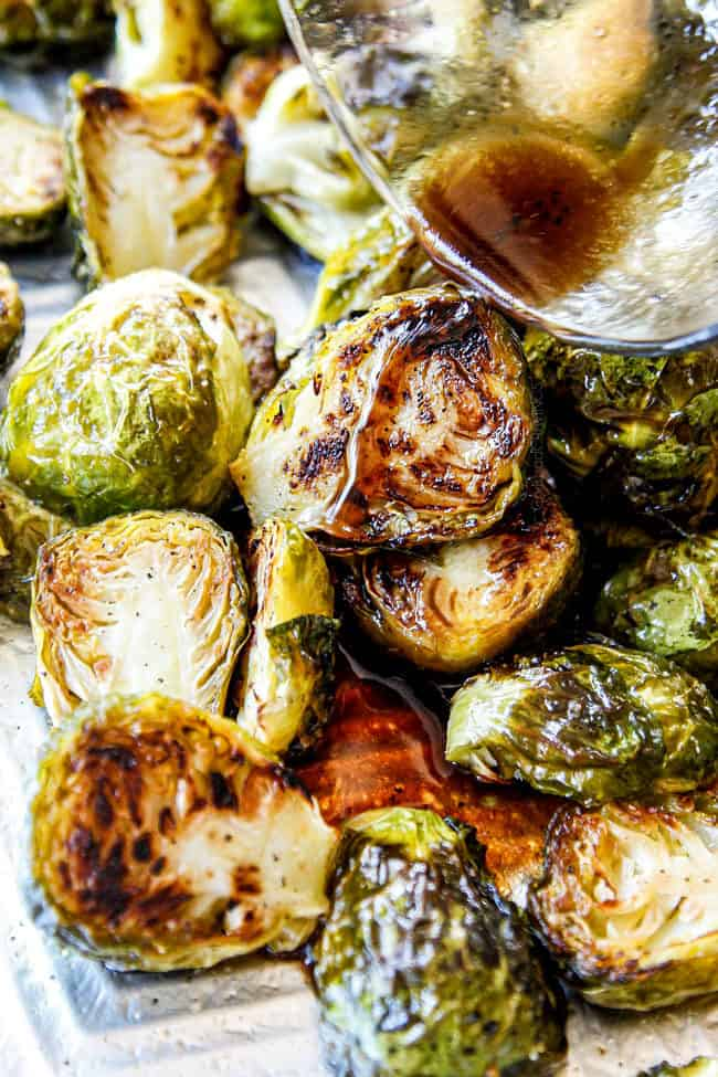 showing how to roast Brussels Sprouts by pouring balsamic over Roasted Brussels Sprouts