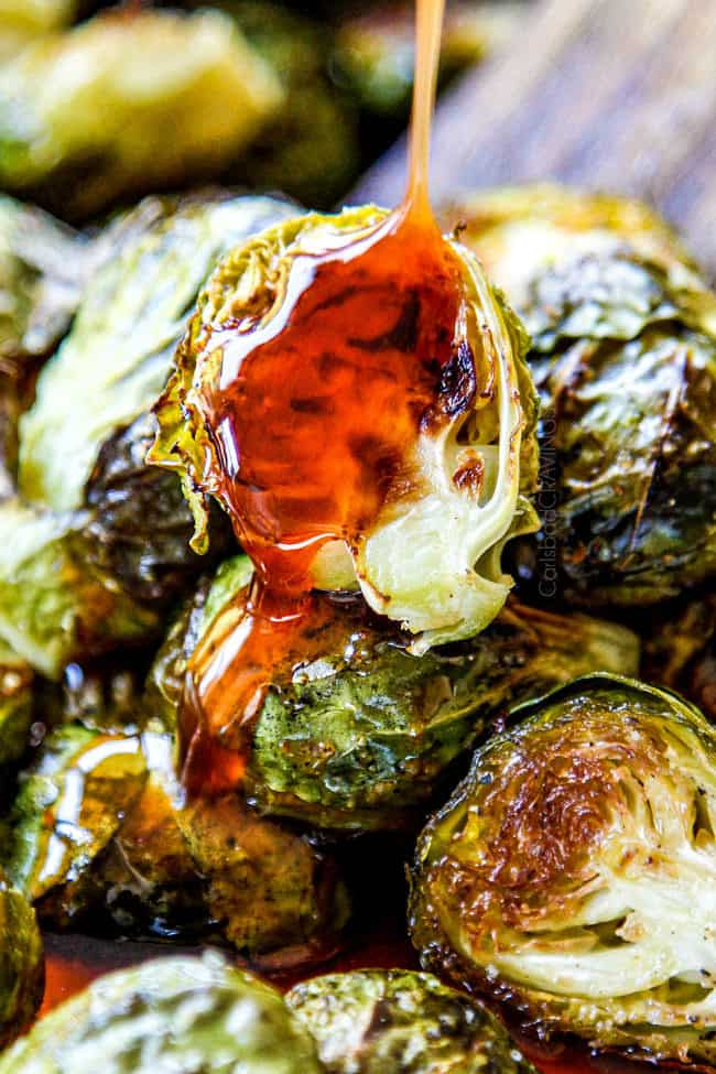showing how to cook Brussels Sprouts recipe in oven by drizzling honey sriracha over oven Roasted Brussels Sprouts