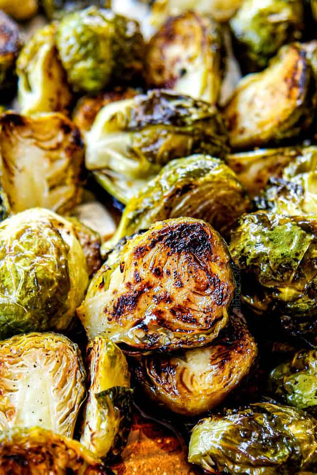 tossing Baked Brussels Sprouts on a baking sheet with salt and pepper