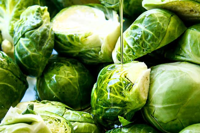 showing how to cook Brussels Sprouts recipe by drizzling with olive oil on a baking sheet