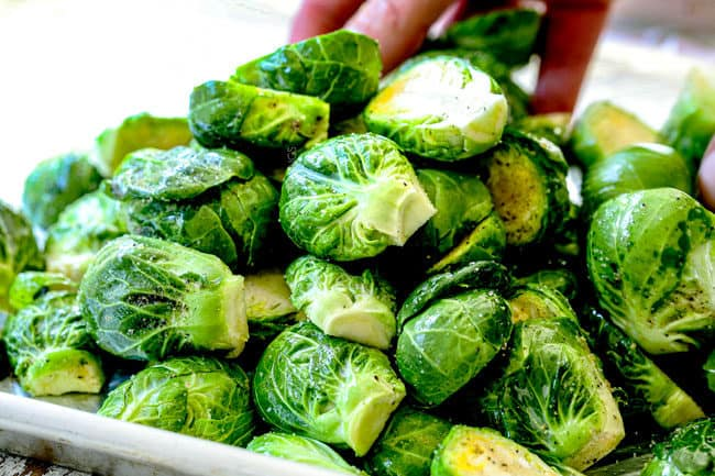 showing how to make Brussels Sprouts recipe in oven by tossing sprouts with seasonings