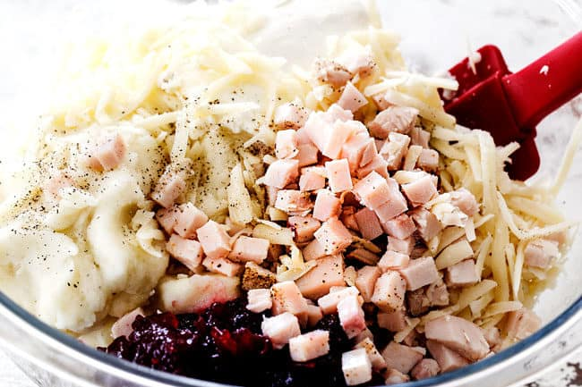 showing how to make leftover turkey recipe by adding chopped turkey, mashed potatoes, and cranberry sauce to a glass bowl
