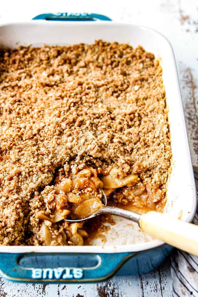 a spoon in a 9x13 pan of the best apple crisp recipe with oatmeal topping