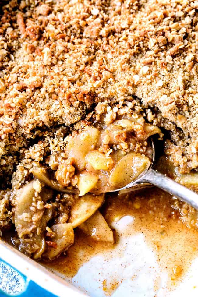 up  close digging into a 9x13 of best apple crisp recipe with oatmeal topping