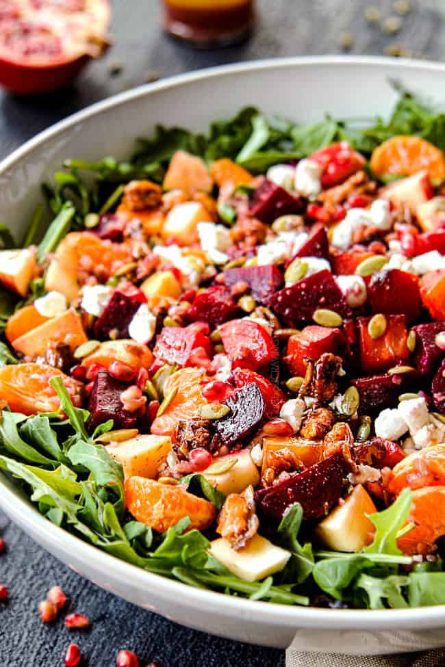 showing how to make roasted beet salad by adding lettuce to a large white bowl followed by cold beets, goat cheese, walnuts, and oranges