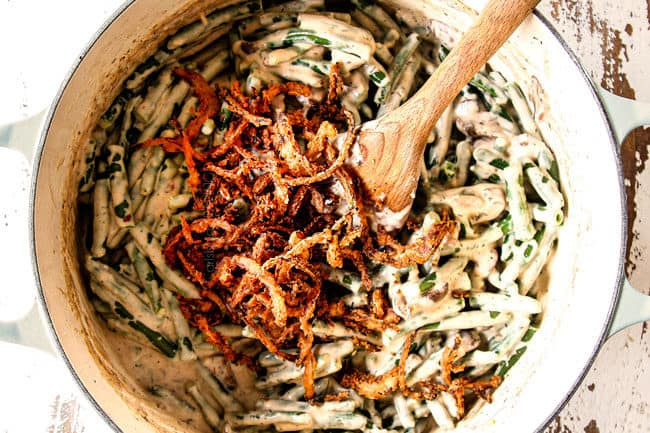 showing how to make best green bean casserole by adding fried onions to creamy green beans