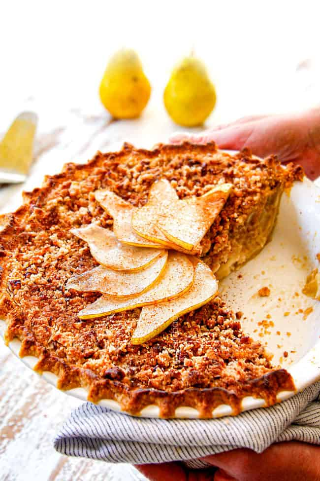 two hand serving pear pie with streusel topping