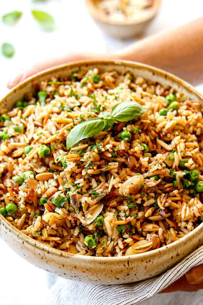 two hands holding easy rice pilaf recipe in a bowl