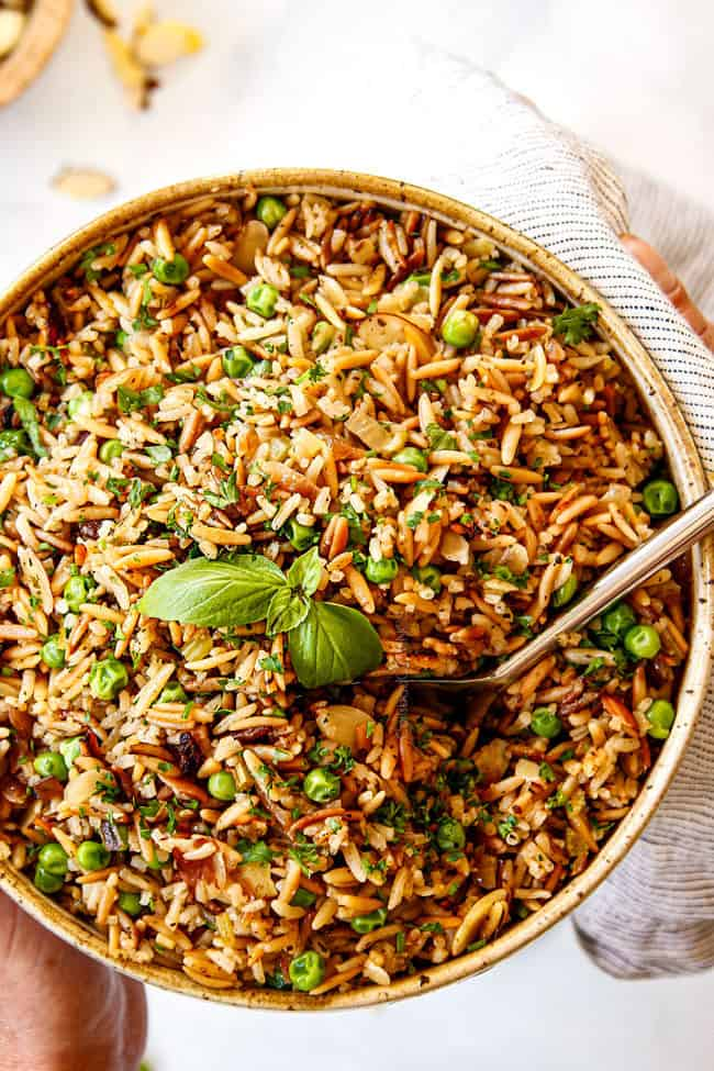 two hands holding a bowl of Rice Pilaf recipe with orzo