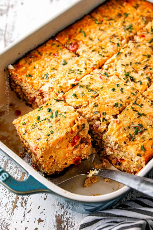 a pan of overnight breakfast casserole recipe with a spatula picking up a slice