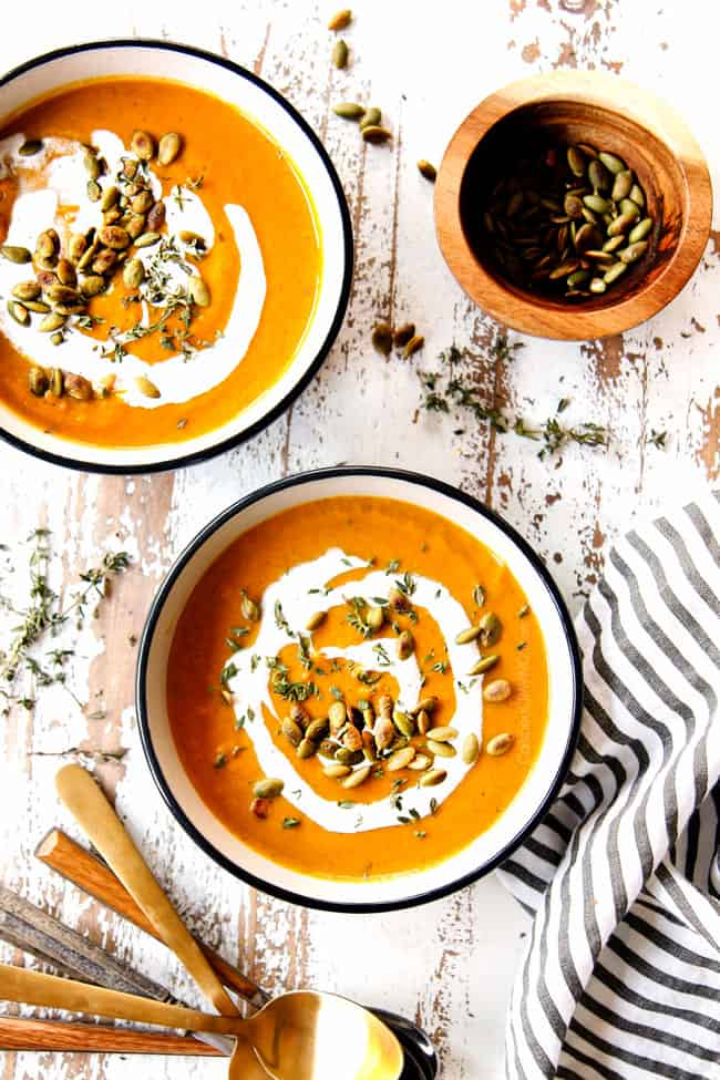 top view of two bowls of easy butternut squash soup garnished with pumpkin seeds and heavy cream