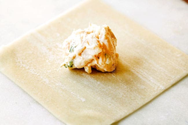 showing how to make crab rangoon by adding filling to center of wonton wrapper