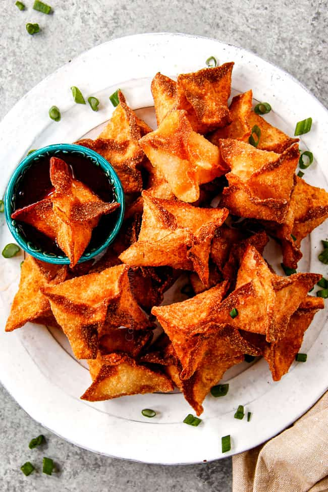 top view of crab rangoon recipe on a platter with sweet and sour sauce