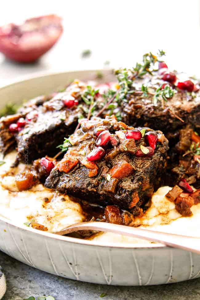 up close of beef short ribs recipe in a white bowl garnished with thyme