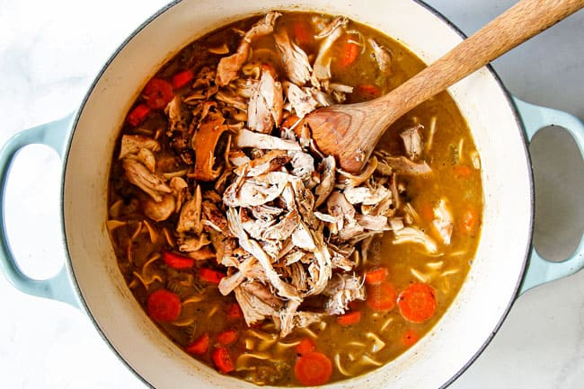 showing how to make chicken noodle soup by adding shredded chicken and egg noodles to soup