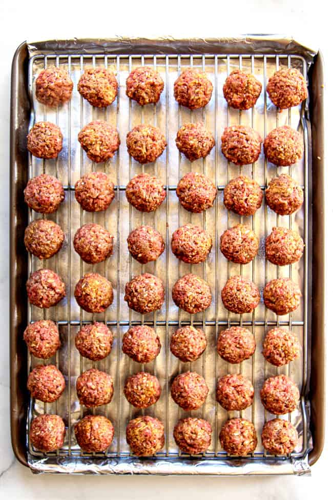 top view showing how to make easy cocktail meatball recipe by lining unbaked meatballs on a baking rack so they aren't touching