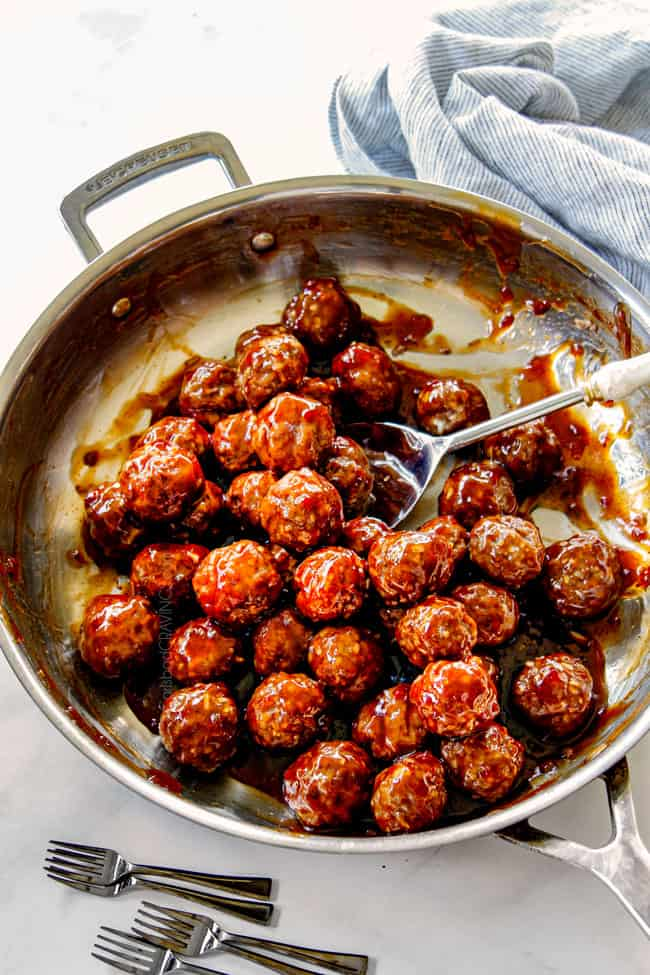 showing how to make cocktail meatball recipe by tossing meatballs with sauce in a skillet