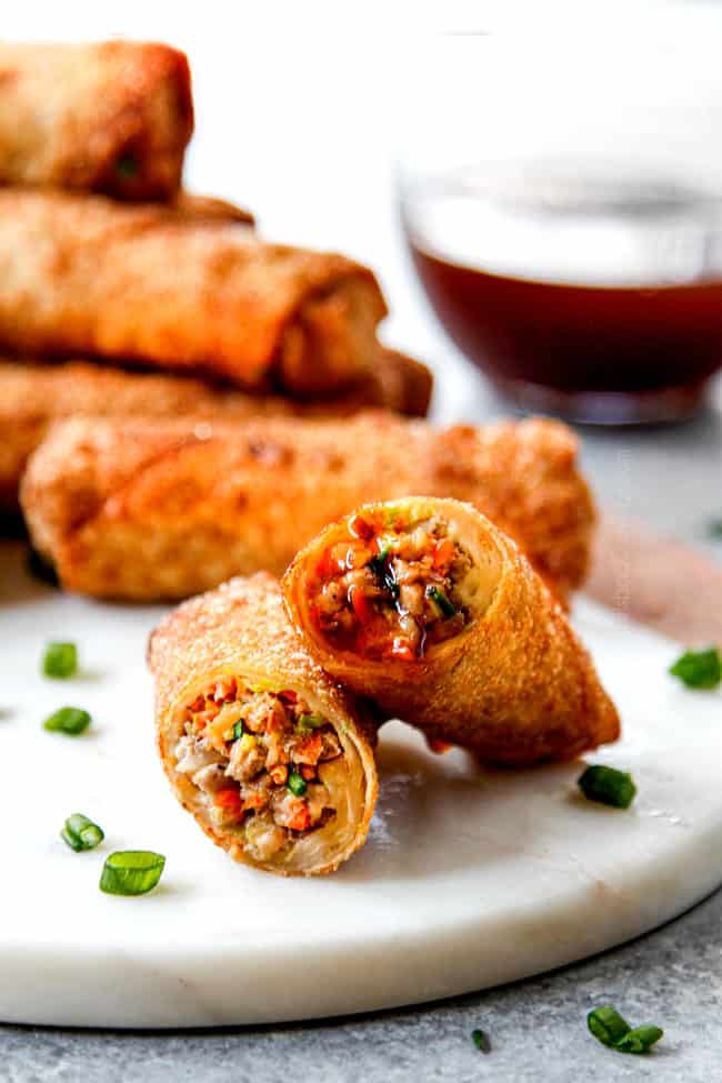 two homemade egg rolls stacked after being dipped in dipping sauce