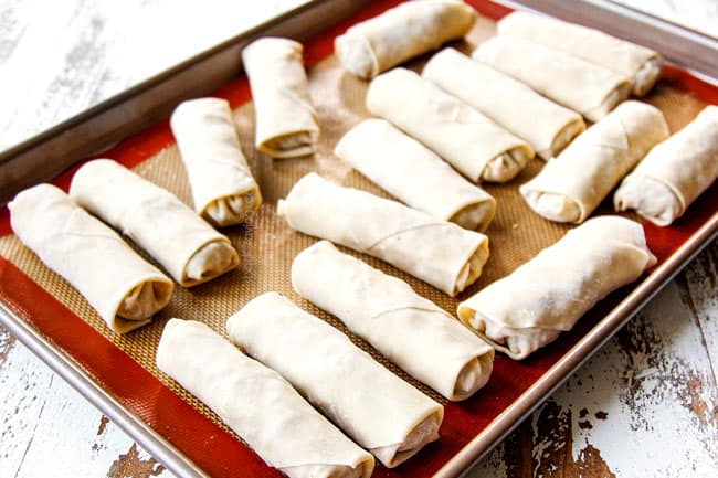 showing how to make homemade egg rolls by storing on a nonstick mat until ready to fry