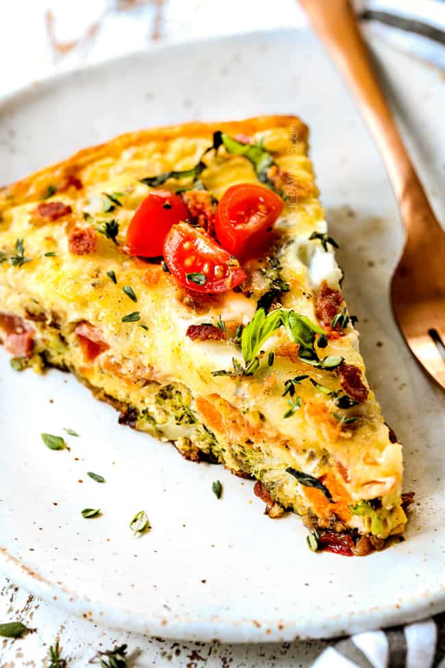 showing how to serve frittata recipe by placing a slice on a plate and garnishing with basil and tomatoes