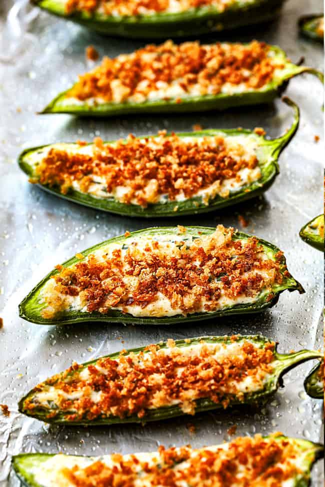 showing how to make homemade jalapeno popper recipe by lining poppers up in a row on a baking sheet
