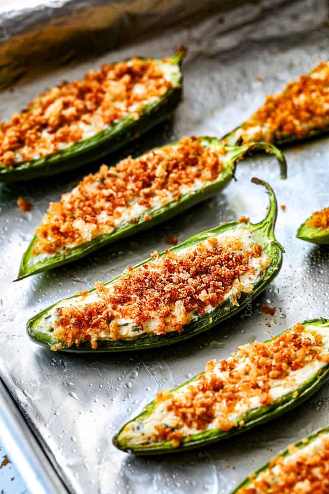showing how to make baked jalapeno poppers by lining them on a baking sheet with foil