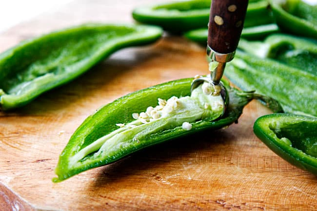 showing how to make easy jalapeno poppers by removing the seeds and ribs using a teaspoon