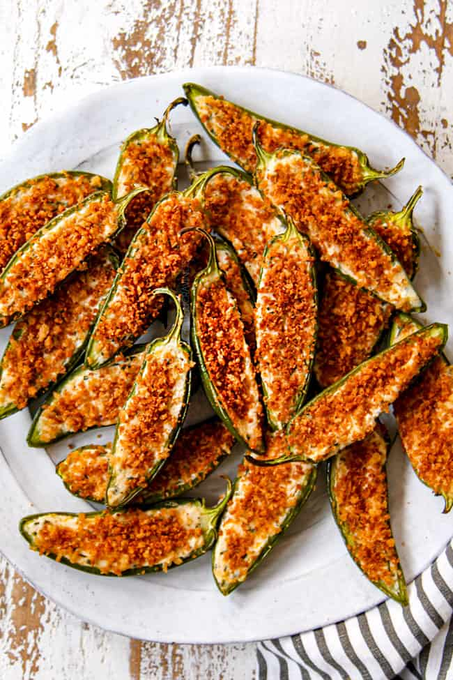 showing how to serve homemade jalapeno poppers by placing on a plate with dip