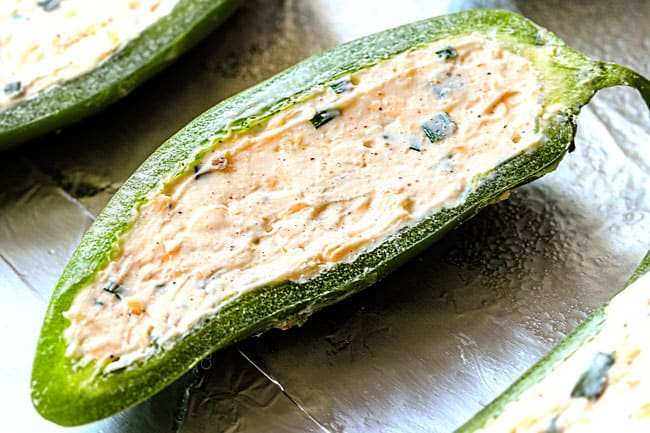 showing how to make jalapeno poppers by stuffing with cream cheese filling