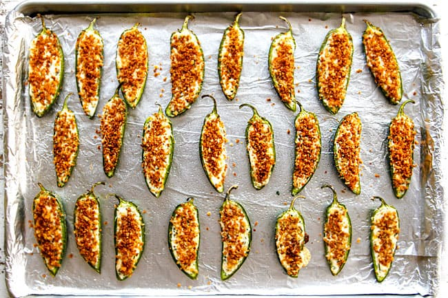 showing how to make jalapeno poppers by lining jalapeno poppers on a baking sheet to bake